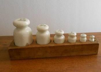 Odważniki porcelanowe w stojaku drewnianym.